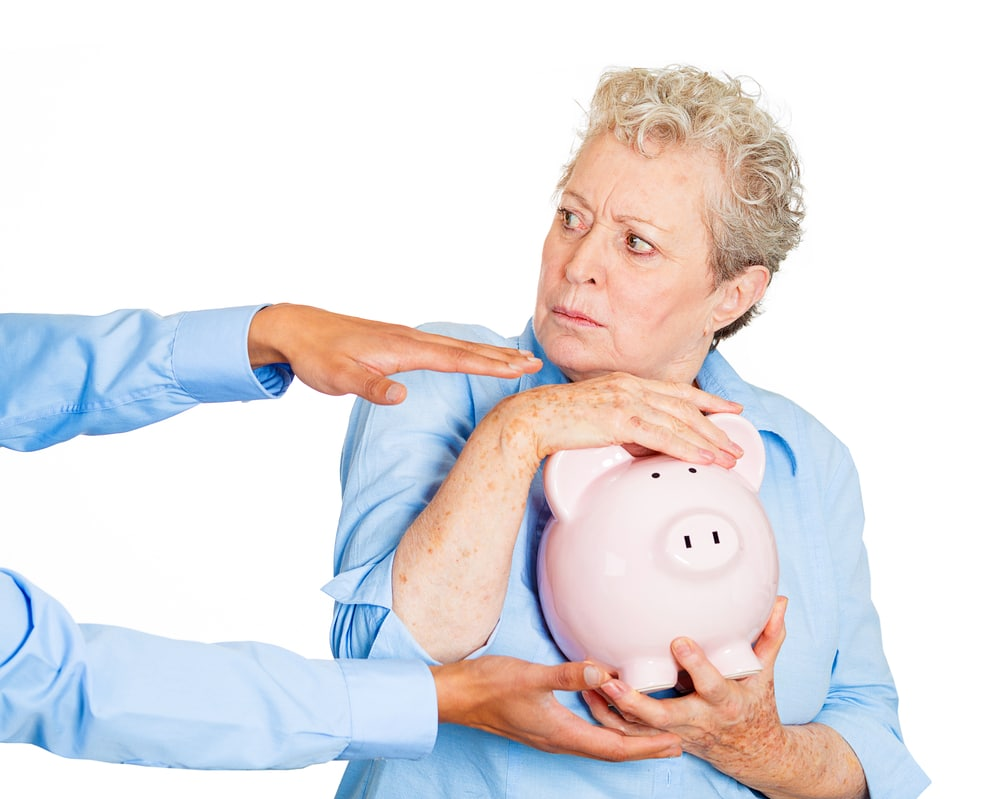 Lady in blue shirt clutching piggy bank while someone else reaches for it