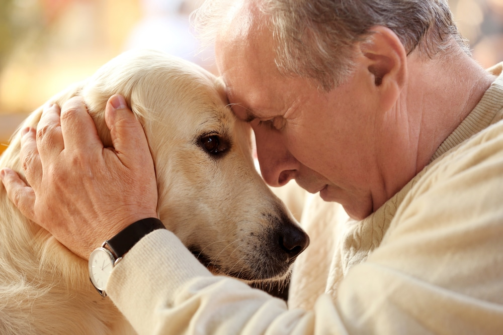 Man leaning his head against his dog's head
