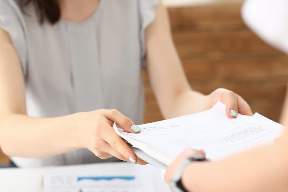 Woman handing another person paperwork