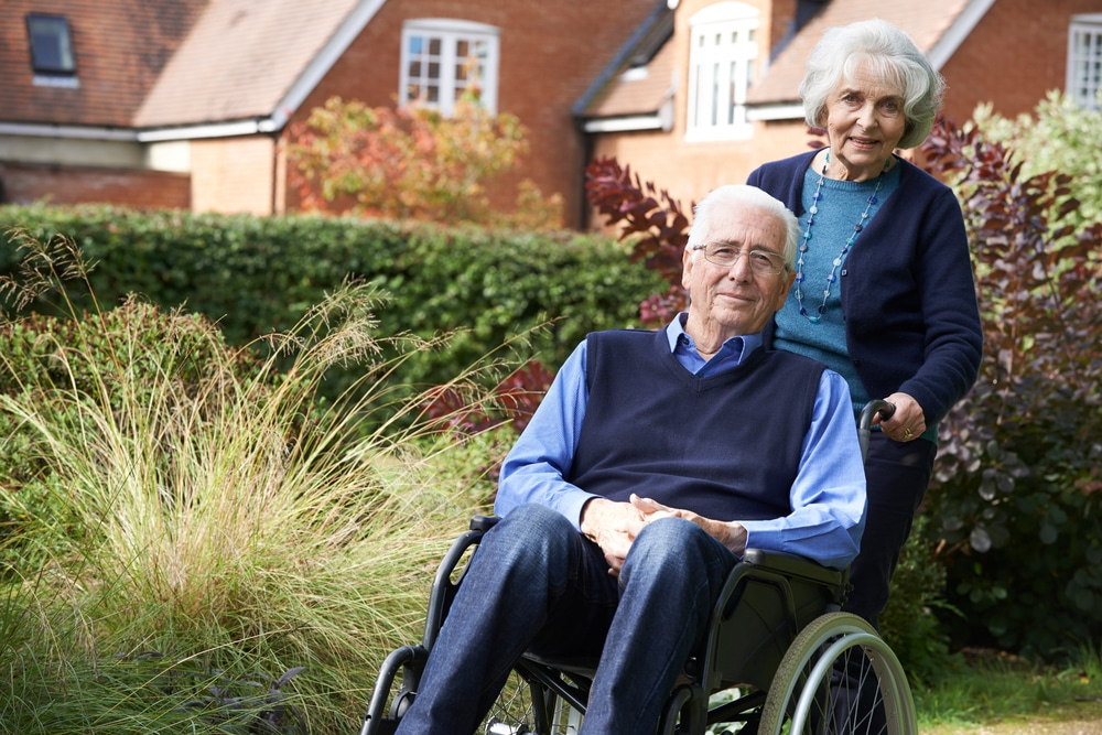 Elderly woman standing behind elderly man who is seated in a wheelchair