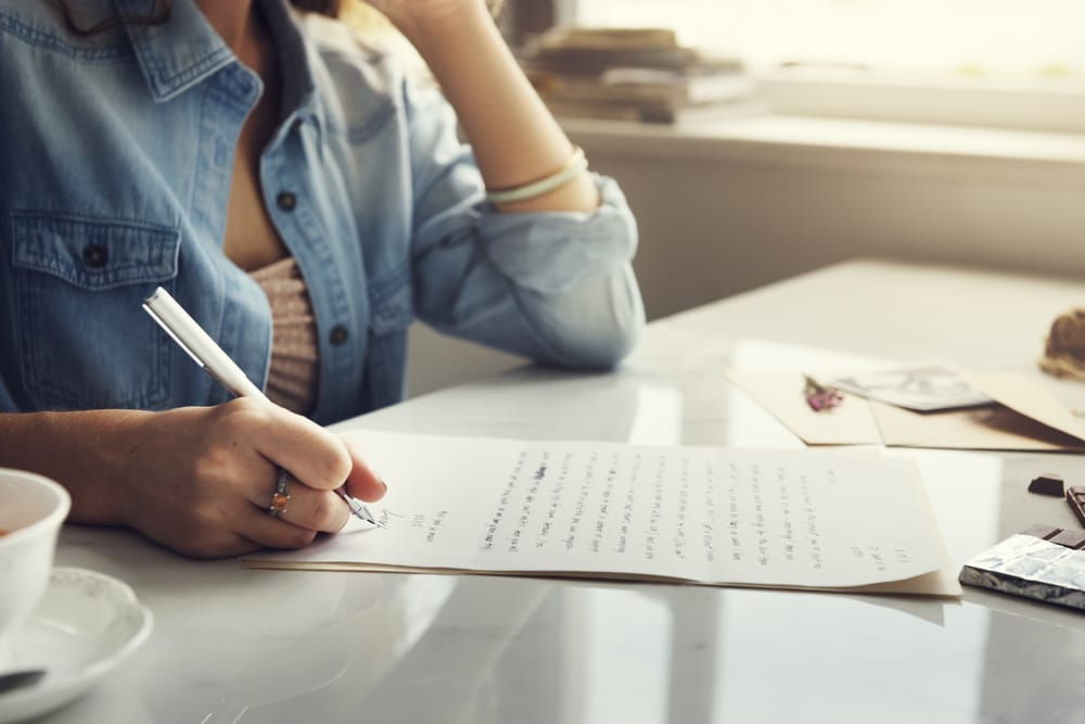 Woman sitting at a table and writing a letter