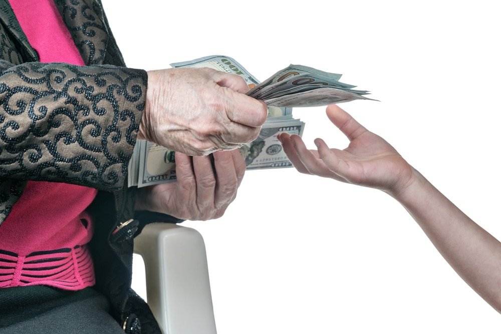 Elderly lady handing $100 bills to younger person