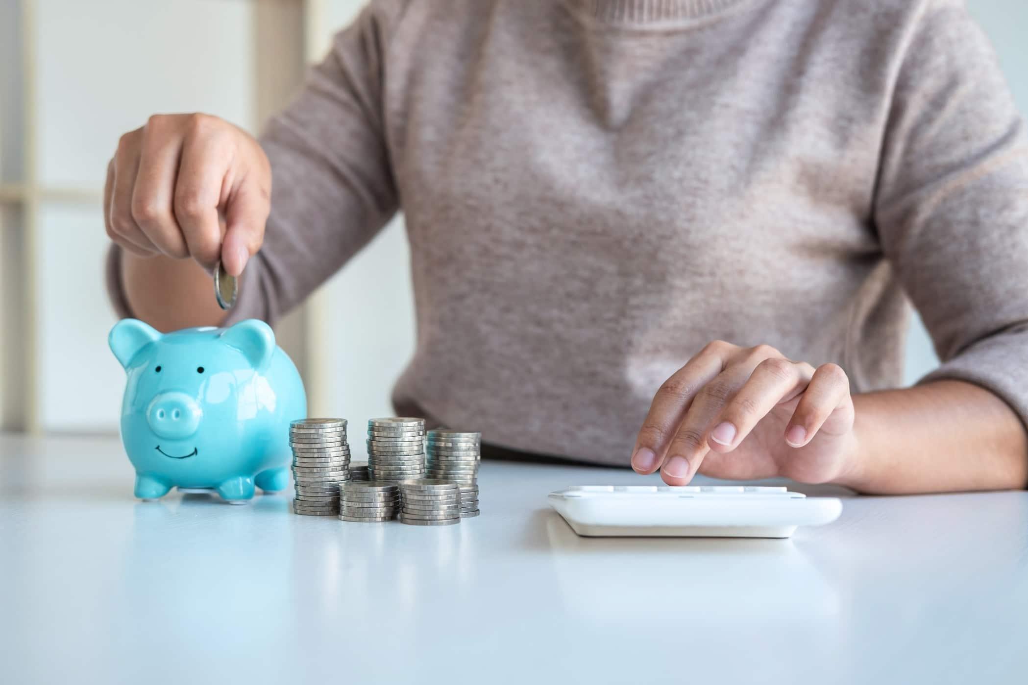 Woman putting coins into a blue piggy bank