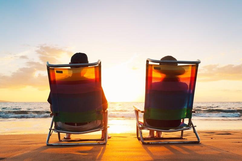 Happy Retired Couple Enjoying Beautiful Sunset At The Beach