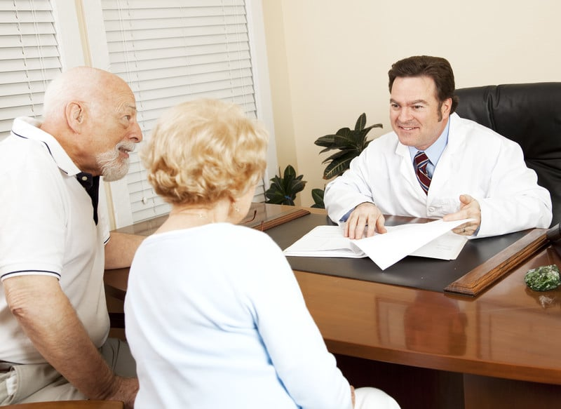 Doctor sitting across a desk from a senior couple gives them good news