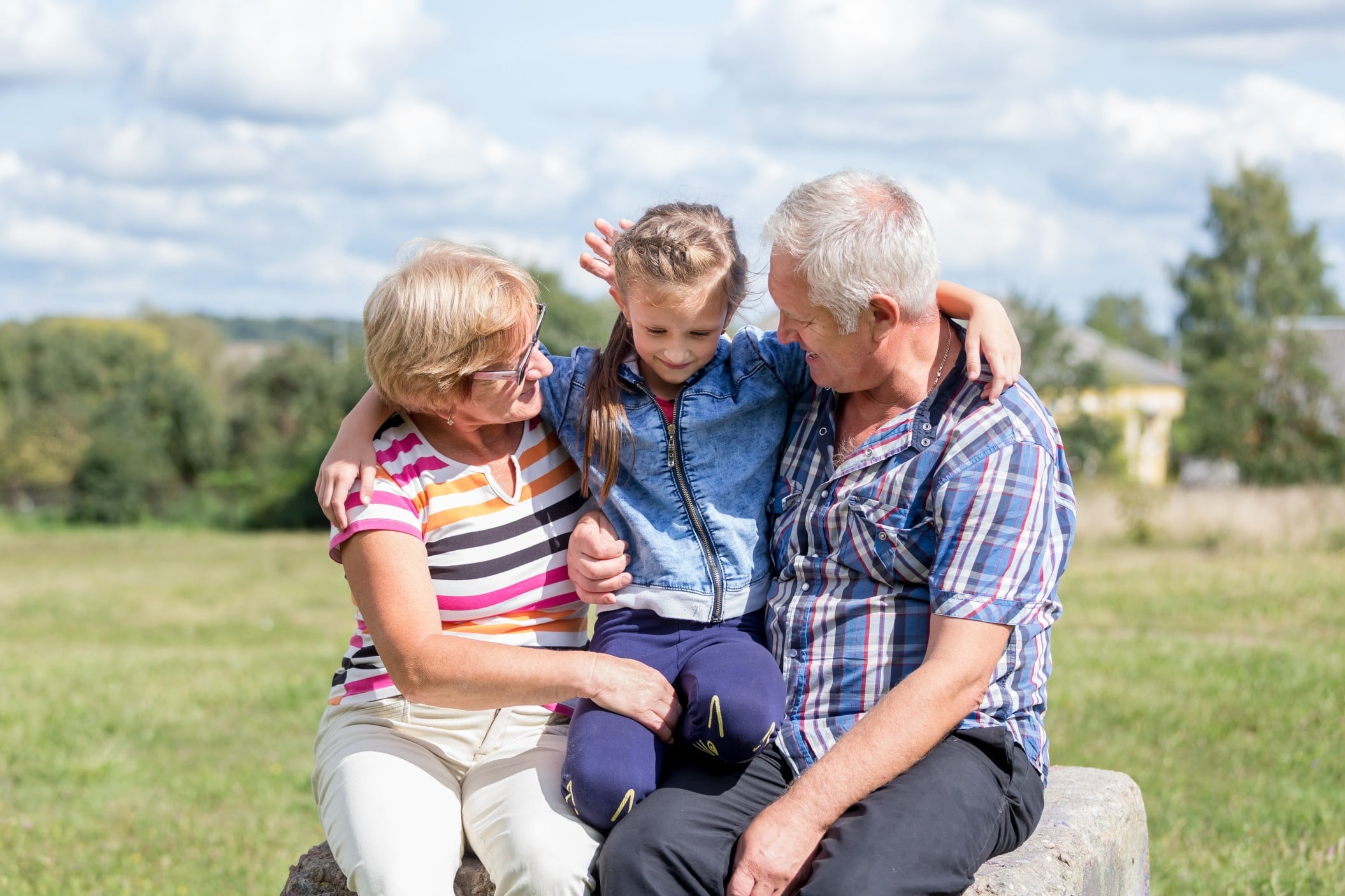 Grandparents with Granddaughter in a grassy field on a sunny day