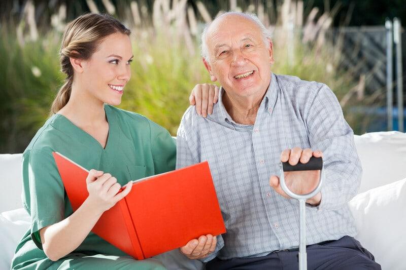 Portrait of happy senior man sitting by female nurse holding book