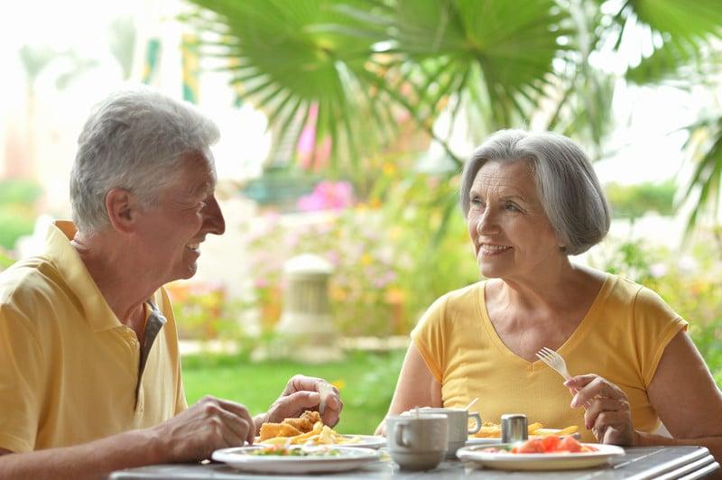 Senior couple eat outside