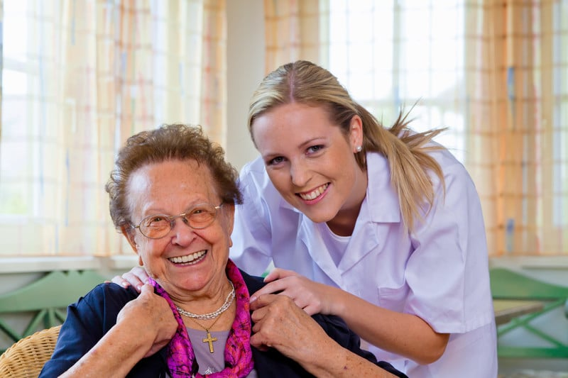 Senior woman smiling with a nurse at assisted living facility