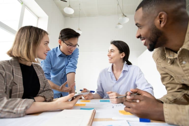 Four people actively discussing startup business