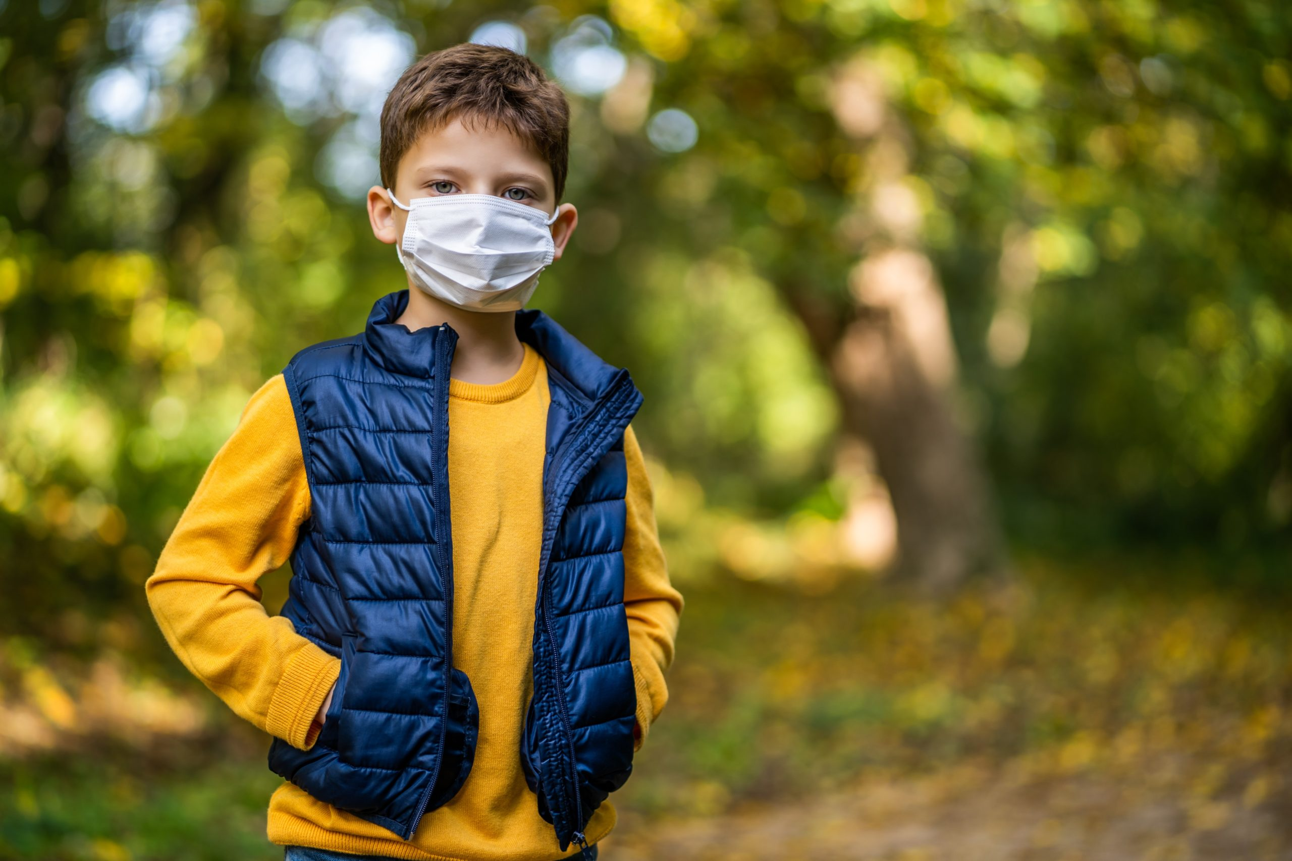 Boy wearing yellow shirt, navy blue vest, and face mask