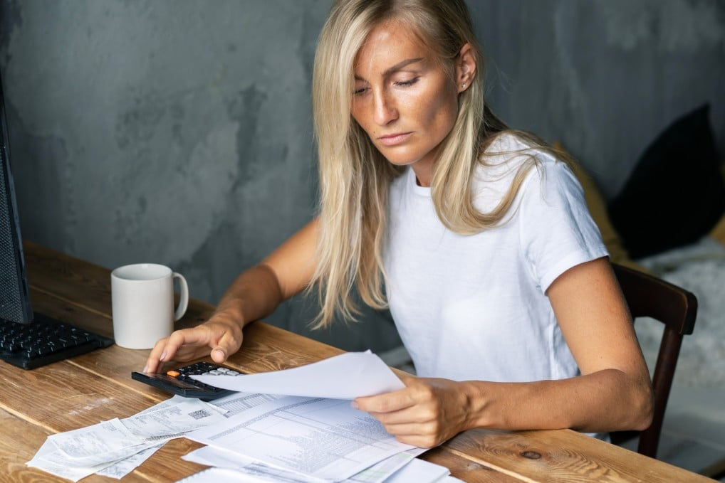 Woman in a white shirt sitting at a desk holding a calculator and reviewing a stack of bills