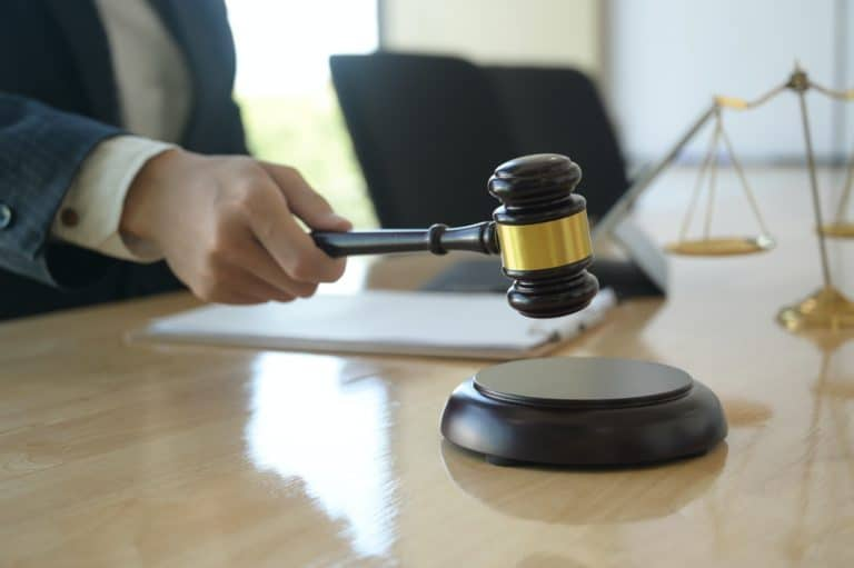 Lady holding a gavel hitting on a wooden stand placed on table; scales of justice in the background