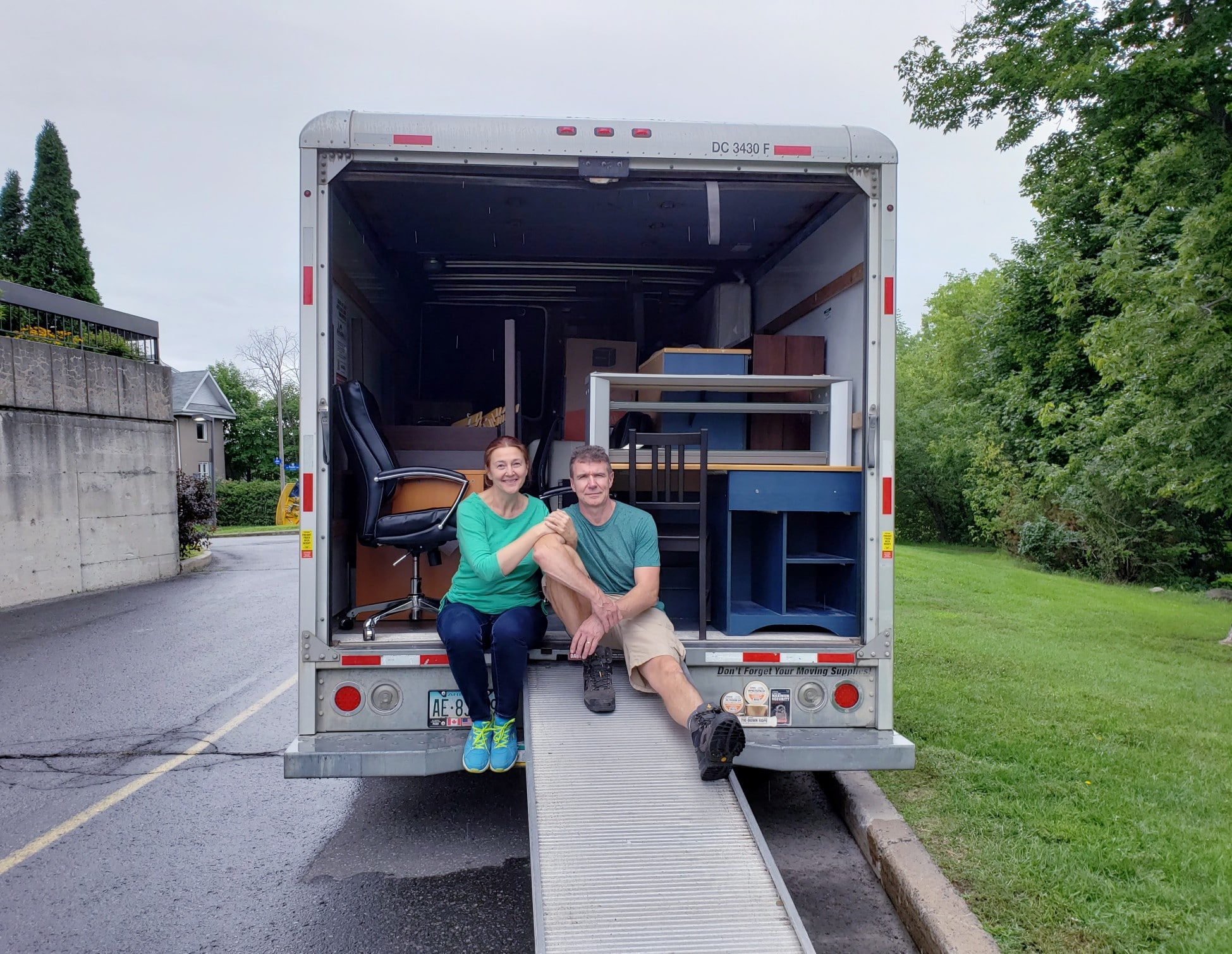 Couple is ready to move into new place--sitting on a moving truck filled with furniture