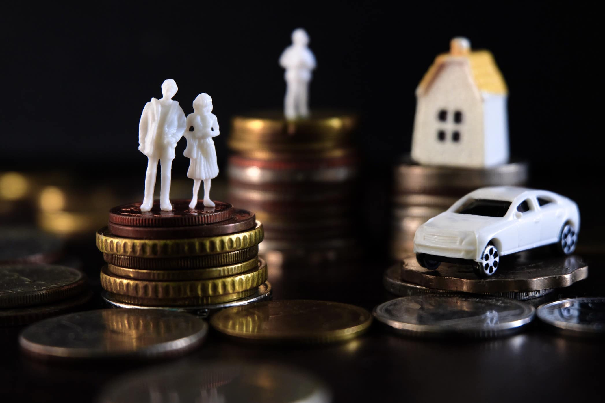 Coins stacked with house sculpture and model car on top with black background