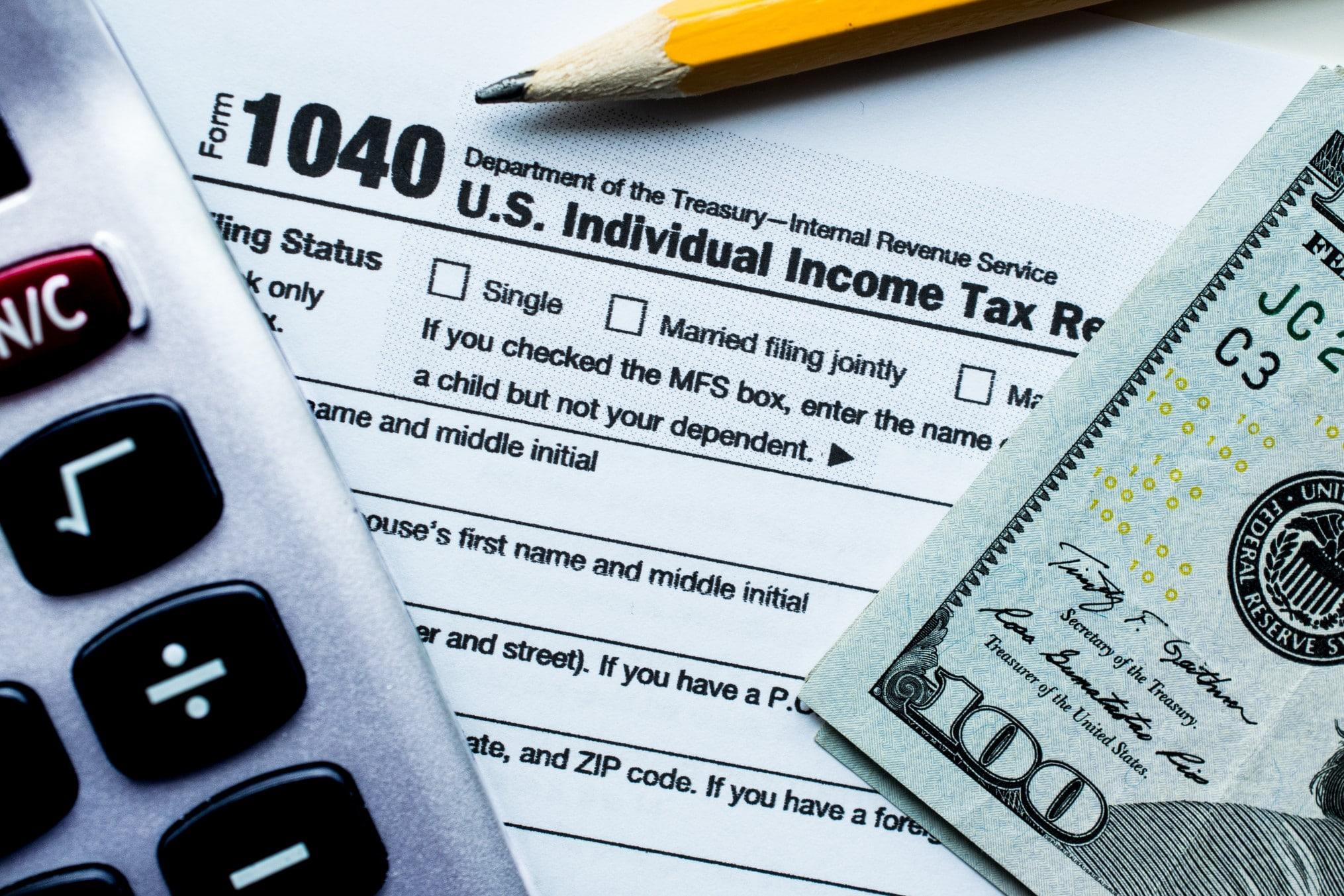 A calculator, a 1040 tax form, a $100 bill, and a pencil