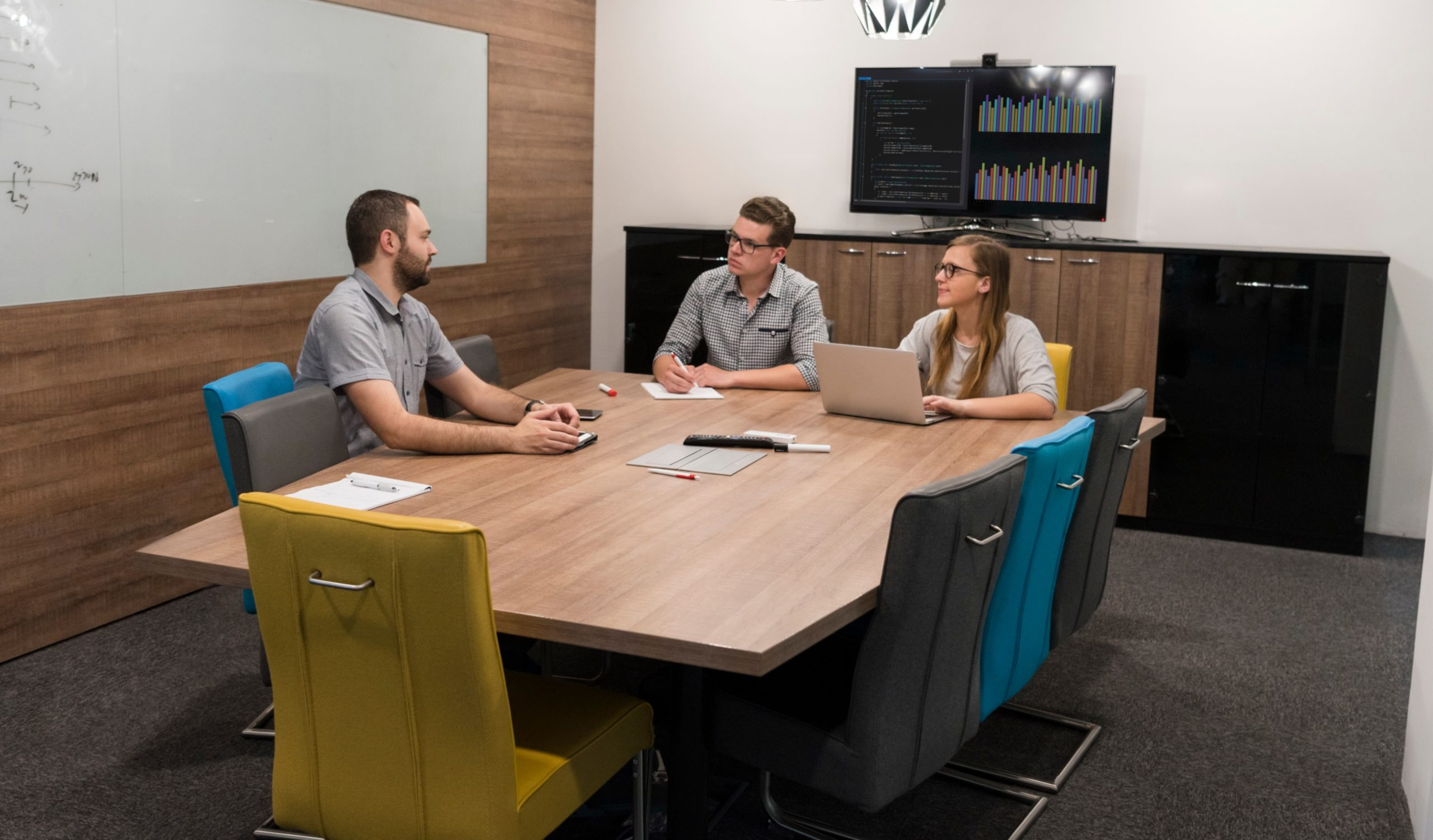 Three people sitting around a conference room table